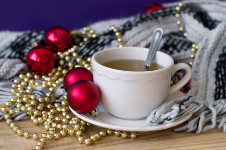 Green tea in white small cup and red christmas balls and golden chain for home decoration. Christmas morning concept