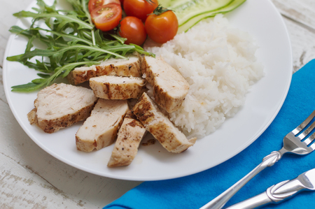 Healthy and balanced meal: baked chicken breast, rice, cucumber, cherry tomatoes and rocket (arugula) leaves Stock Photo