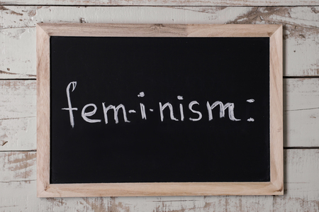 The word feminism written on blackboard. Womens rights concept. Feminism movement