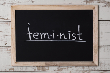 The word feminist written on chalkboard. Womens rights movement. Feminism concept