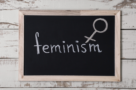 The word feminism and venus symbol at blackboard, top view Stock Photo