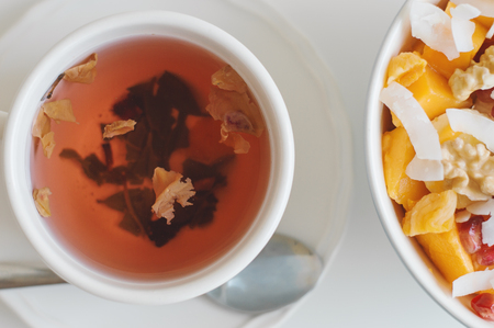 Green tea with hibiscus and rose petals served with a bowl with fresh fruit salad. Healthy vegan breakfast 写真素材