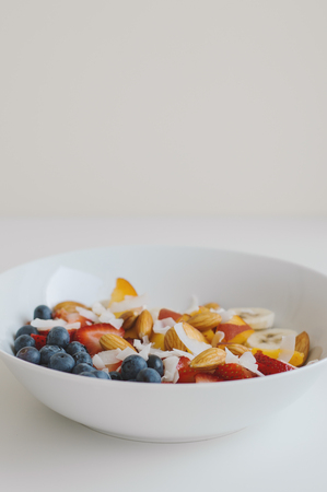 Vertical photo of healthy breakfast with oats, blueberry, peach, strawberry, almond, banana and coconut. Healthy and balanced meal with healthy carbs