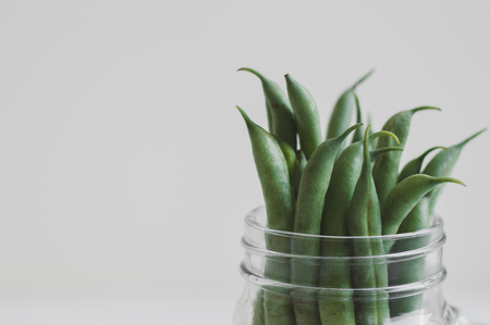 Fresh green beans in a jar on white background. Food ingredient. Raw plant