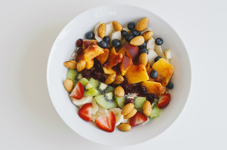 White bowl with healthy and sweet breakfast: oats, strawberry, kiwi, peach, banana, dried cranberries, blueberry and almond, top view