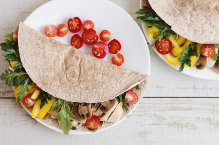 Serving of healthy sandwich with chicken meat and vegetables. Whole wheat wrap with chicken breast, mushroom, red cherry tomato, yellow bell pepper, parsley, arugula