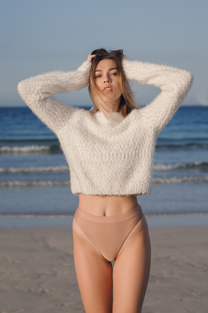 Young european female in beige bikini and white casual sweater posing at the beach, sand and sea as background. Woman with slim and lean body. Relax and leisure