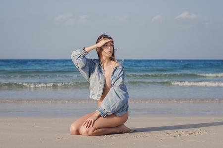 Young female model sitting on an empty beach by the ocean with waves and looking for something. Woman in beige casual swimwear and denim jacket