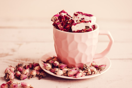 Turkish delight in a small coffee cup and dried rose buds. Nougat with flower petals