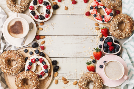 Breakfast bagels with oats and sunflower seeds served with cream cheese and fresh berries and cappuccino coffee. Breakfast menu