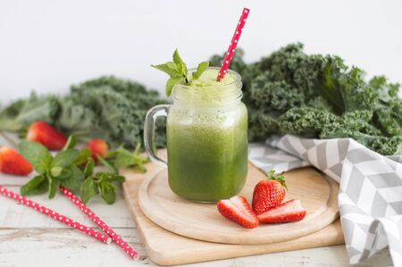 Green smoothie with kale and strawberry served with a red paper straw. Healthy detox drink