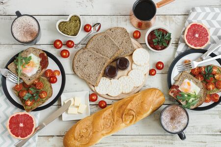 Breakfast food served for two people. Pesto toasts, egg, bread, baguette, crackers, jam, grapefruit and coffee, top view. Breakfast concept Reklamní fotografie