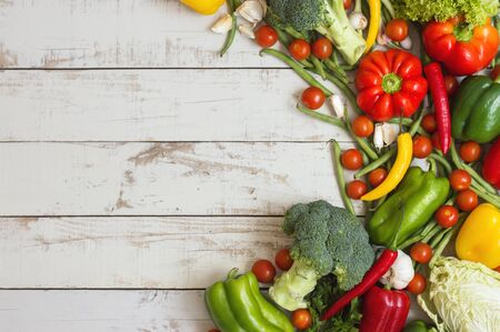 Horizontal background with a variety of seasonal vegetables. Green beans, cherry tomatoes, bell pepper, broccoli, lettuce and cabbage on wooden table