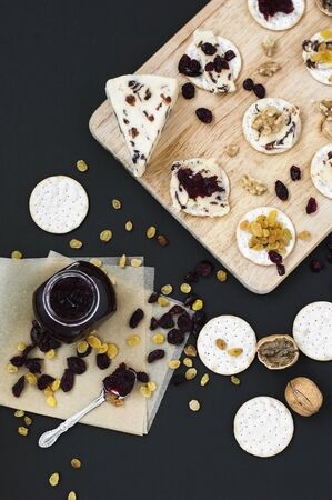 Cheese platter with homemade cranberry cheese, jam, crackers, walnut, raisin and dried cranberry, top view Reklamní fotografie