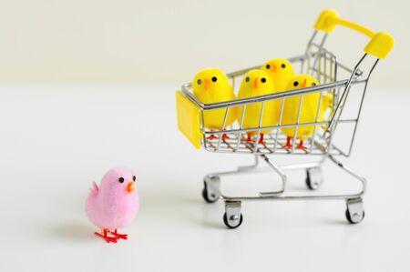 Ein rosa Baby-Huhn-Spielzeug, das auf weißem Hintergrund steht, und vier kleine Baby-Huhn-Spielzeuge in einem Einkaufswagen. Führungskonzept