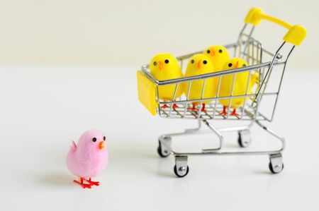 One pink baby chicken toy standing on white background and four small baby chicken toys in a shopping cart. Leadership concept