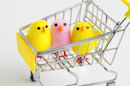 Baby chicken toys of yellow and pink color in a small shopping cart. Funny decoration. Easter shopping. Diversity concept Stockfoto