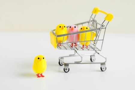 Small baby chicken toys of yellow and pink color in a shopping cart and one toy standing on white background in front of the cart. Easter decoration Stockfoto