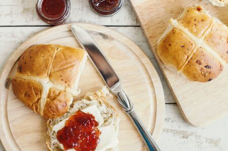 Traditional Easter hot cross buns with butter and jam served on a wooden board. Festive breakfast