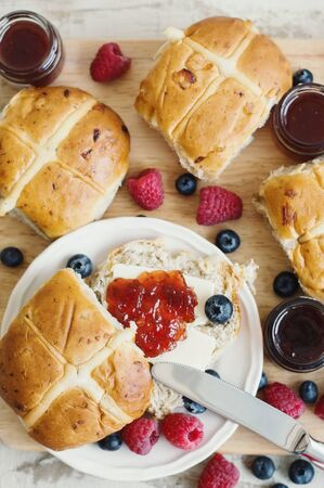 Easter breakfast: homemade hot cross buns with jam, butter, blueberry and raspberry, top view.