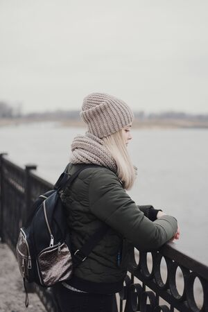 Young female with blond hair dressed in khaki jacket, knitted scarf, hat and with backpack standing at waterfront promenade and looking at river in a rainy day Foto de archivo