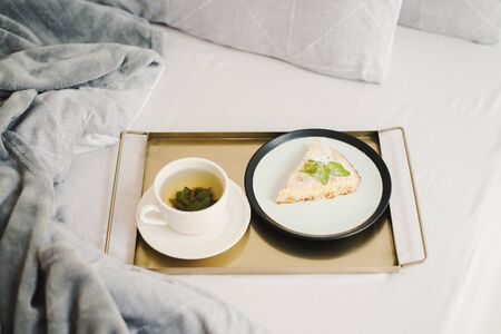 Homemade apple pie with powdered sugar and mint and a cup of mint tea served on a metal tray. Breakfast in bed. Morning dessert