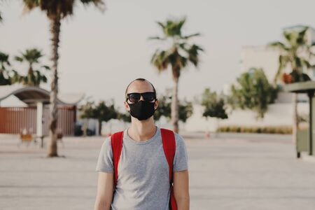 Young male traveler with backpack and in sun glasses wearing black protective mask. Covid 19 or coronavirus pandemic concept. Man in a dust protection reusable  mask Archivio Fotografico