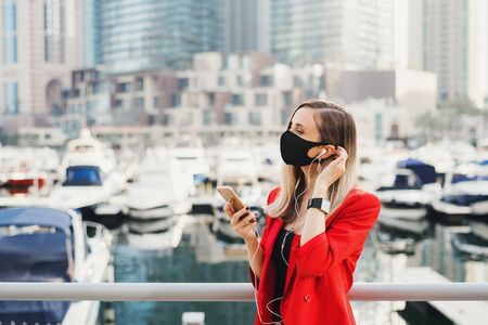 Young businesswoman in red suit wearing protective face mask of black color standing at city business center and calling via earphones. Social distance concept. New normal after Covid 19 pandemic