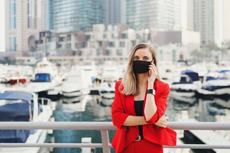 Young woman in red suit wearing reusable face mask of black color standing in city center and making a call via a smartphone. Female entrepreneur during Covid 19 or coronavirus pandemic 스톡 콘텐츠