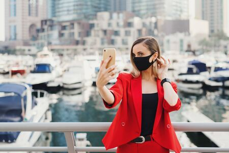 European woman in red suit wearing black protective face mask taking a selfie photo at city street near yachts and skyscrapers. Fashion blogger concept 스톡 콘텐츠