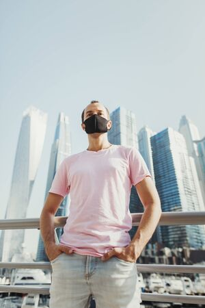 Young man in blue jeans and pink t-shirt wearing protective face mask of black color and standing in city business center with office buildings. Prevention of Covid 19
