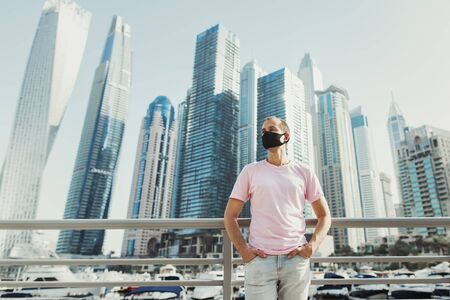 Young european man wearing pink t-shirt, jeans and protective face mask and standing near yachts and skyscrapers at city's promenade. Travel during Covid 19 or Coronavirus pandemic