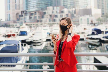 Young european woman with blond hair dressed in stylish red business suit and wearing black face mask standing in front of yachts and skyscrapers in city business center and making a call via smartphone and earphones