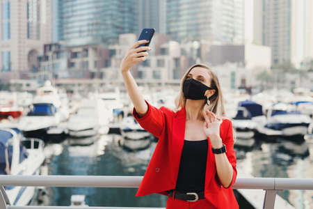 Young woman in red business suit wearing protective face mask of black color taking a selfie photo near yachts and skyscrapers in city center. Travel during Covid 19 or coronavirus pandemic