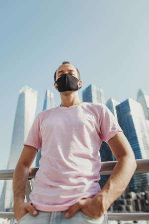 Confident young man in pink t-shirt and jeans wearing protective face mask of black color. Male tourist standing at city business center during Covid 19 pandemic Stok Fotoğraf