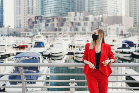 Young european female in red suit wearing black protective face mask standing at the city promenade near yachts and skyscrapers. Social distance and New normal during Covid 19 outbreak
