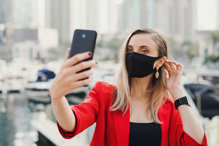 Young woman in red jacket wearing protective face mask of black color taking a selfie photo outdoors. Female tourist during Covid 19 pandemic