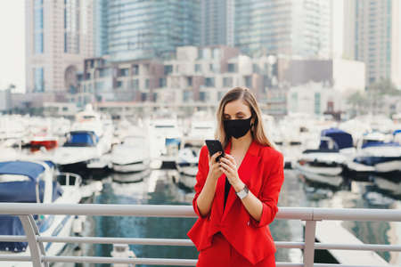 Young female entrepreneur standing at city business center in front of luxury yachts and skyscrapers and looking at smartphone screen. Stylish woman in red suit and protective face mask