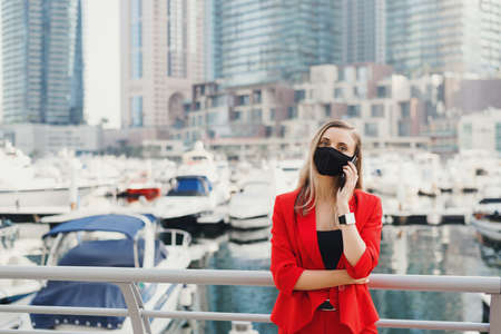 Portrait of young woman in red suit and black protective face mask making a call via a smartphone. Strong and confident female entrepreneur standing in city business center during Covid 19 pandemic Stok Fotoğraf