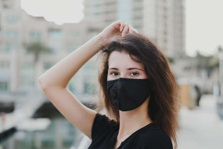 Portrait of woman wearing reusable protective face mask of black color. Air pollution and virus protection concept