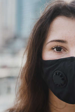 Half face portrait of young woman wearing protective face mask with filter. Air pollution and virus protection. Covid 19 concept