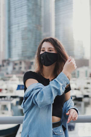 Young european woman with brown hair wearing denim shirt and protective face mask with filter. Female standing at city street during Covid 19 pandemic