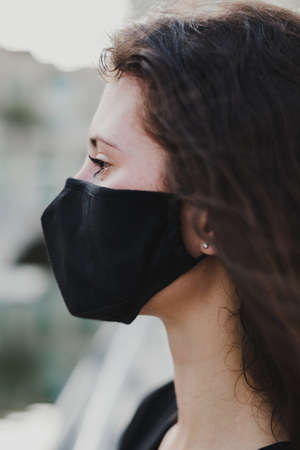 Woman wearing protective face mask of black color. Protection from viruses, dust, air pollution and allergy