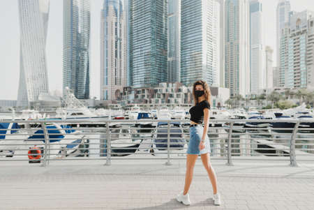 Young woman with brunette hair wearing t-shirt, denim short skirt and reusable face mask and standing at city street. Virus and air pollution protection outside Stok Fotoğraf