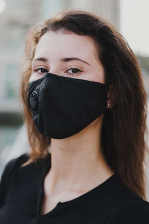 Young female model wearing protective face mask outdoors. Covid 19 protection. Air pollution concept