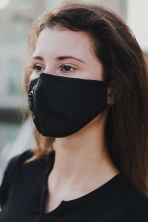 Young woman with brown hair wearing protective face mask with filter. Health protection concept Stok Fotoğraf