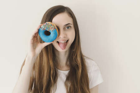 Funny portrait of young European woman holding a blue donut with sprinkles near her eye and showing a tongue