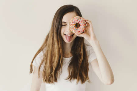 Portrait of cheerful young woman with funny emotion holding a pink donut with sprinkles near her eye Stok Fotoğraf
