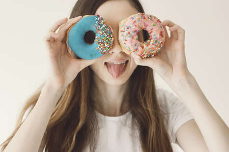 Funny portrait of a young European female model holding blue and pink donuts near eyes and showing a tongue. Positive and cheerful mood Stok Fotoğraf