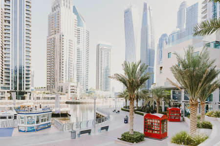 Dubai; UAE - June 6, 2020: Dubai Marina Walk early in the morning. Popular city promenade with skysrapers, cafes, restaurants, hotels, office buildings, yachts and boats cruises Editöryel